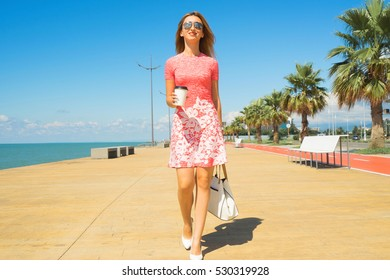 Happy woman in red dress walking on the beach boulevard with coffee cup and handbag.