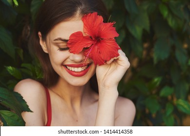 Happy woman with a red flower bright make-up an absentee smile park green leaves Bushes
