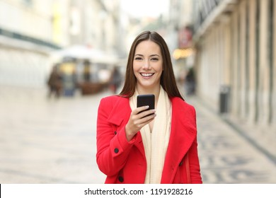 Happy woman in red looking at camera holding a phone in winter in the street