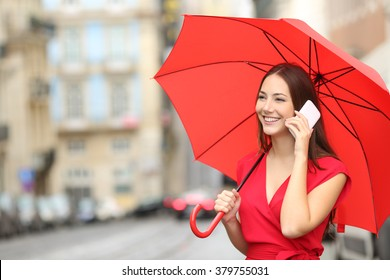 Happy woman in red talking on a smart phone under an umbrella in the street of an old town