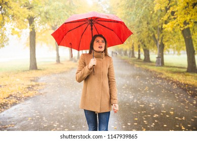 Happy woman with red umbrella walking at the rain in beautiful autumn park. Concept picture