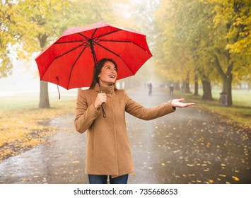 Happy woman with red umbrella walking at the rain in beautiful autumn park