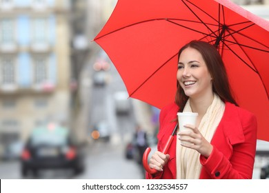Happy woman in red walking with a takeaway drink under an umbrella in the street in a rainy winter