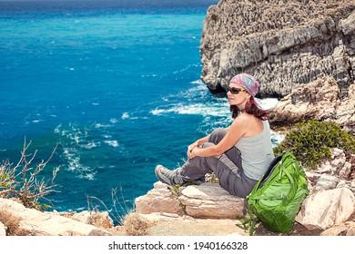 Fröhliche Frau im Entspannen, auf Felsen sitzen und die Reise genießen. Kaukasische Brunette Frau mit Blick nach vorn. Seitenansicht. Hintergrund der schönen Felsen- und Meereslandschaft der südlich kretischen Insel, Griechenland. Europa.