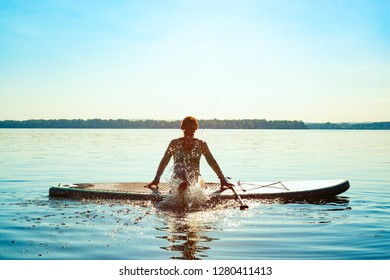 Happy woman relaxes on SUP board and enjoy life. Stand up paddle boarding - awesome active outdoor recreation. Back light.