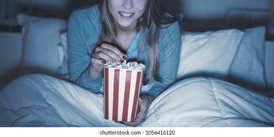 Happy woman relaxing in bed and watching movies on tv late at night, she is eating popcorn