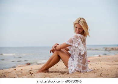 Happy woman relaxing by the sea in the summer