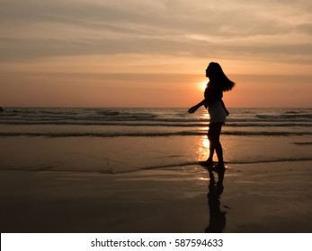 Happy woman relaxing on the beach during sunset.