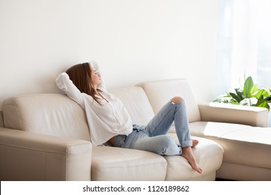 Happy woman relaxing on comfortable soft sofa enjoying stress free weekend at home, calm satisfied girl stretching on couch thinking of pleasant lazy day, dreaming and planning sunday morning