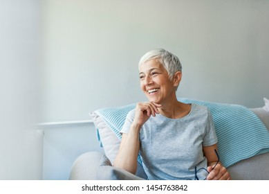 Happy woman relaxing on her couch at home in the sitting room. Portrait of beautiful mature woman smiling while sitting at sofa at home. Beautiful middle age woman smiling at home