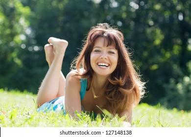 Happy   woman  relaxing outdoor in grass