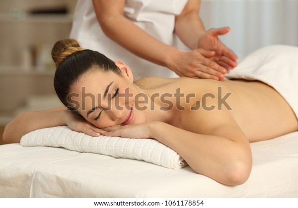 Happy woman relaxing receiving a massage in a spa salon