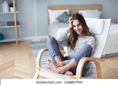Happy woman resting comfortably sitting on modern chair in the living room at home. Lifestyle.