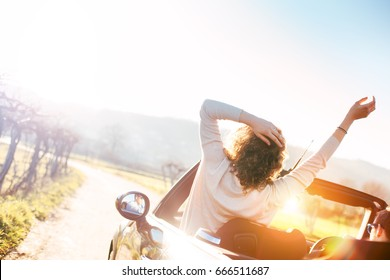 Happy woman resting in a convertible at sunset enjoying the view