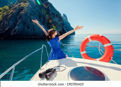 Happy woman resting on the nose boats at sea. Water activities.