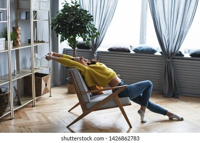 Happy woman resting sitting in a comfortable chair. Enjoying time at home.