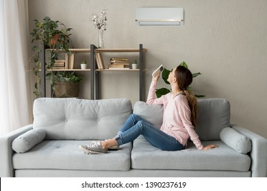 Happy woman rests on couch in modern cozy living room looks up on wall holds cooler system remote controller air conditioner user enjoy fresh air in hot summer day, set comfortable temperature indoors