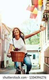 Happy woman riding the bike along the city street, in summer sunny day, smiling of joy during outdoor activity.