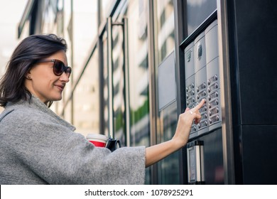Happy woman ringing on doorbell while using intercom at residential building entrance.