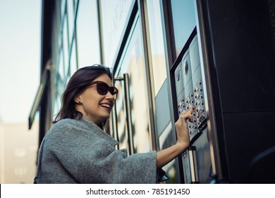 Happy woman ringing on doorbell at building entrance. Using intercom.