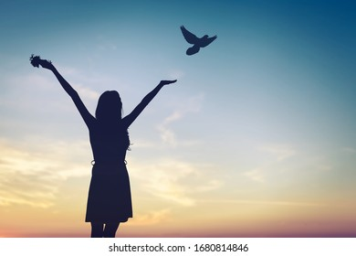 Happy woman rise hand and birds on sky background