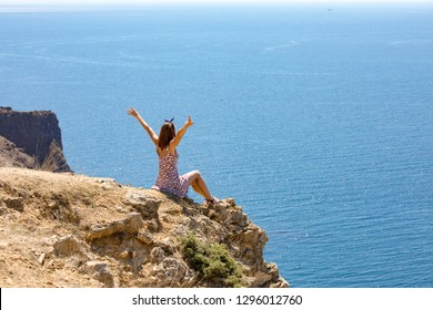 Happy woman from the rock looks at the sea and raises her hands up. General rear view. Freedom