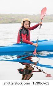 Happy woman rowing on lake in a kayak smiling at camera