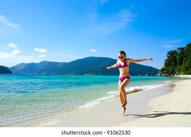 Happy Woman running along tropical island beach