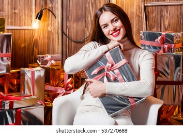Happy woman in Santa hat with Christmas gift