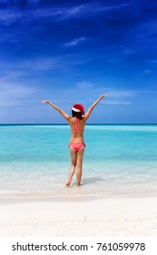 Happy woman with a Santa hat enjoys the turqoise waters of the tropics
