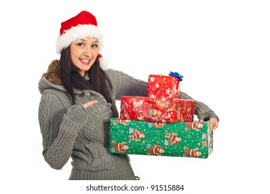 Happy woman with Santa hat pointing to her Christmas gifts isolated on white background