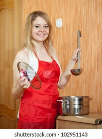 Happy woman with  saucepan at her kitchen
