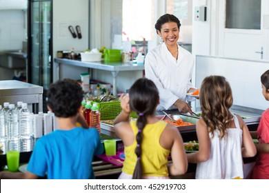 Happy woman serving food to schoolchildren in canteen