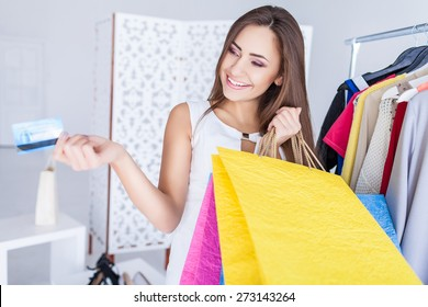 Happy woman in shop with a credit card in a hand