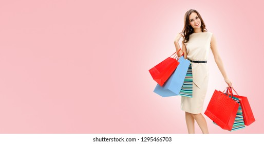 Happy woman with shopping bags, against pink background, with copy space for some slogan, advertising or text message