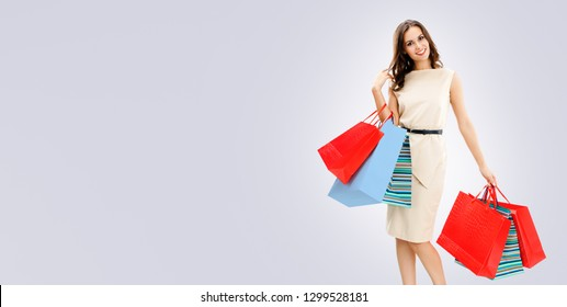Happy woman with shopping bags, against grey background, with copy space for some slogan, advertising or text message