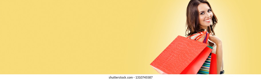 Happy woman with shopping bags, against yellow color background, with copy space for some slogan, advertising or text message