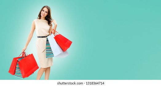 Happy woman with shopping bags, against blue background, with copy space for some slogan, advertising or text message