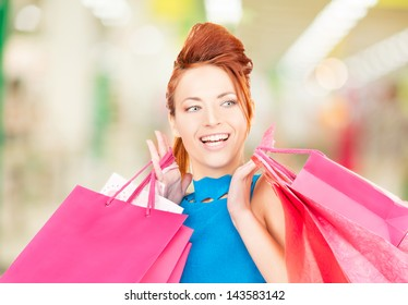happy woman with shopping bags at the mall
