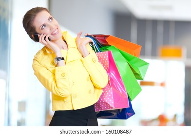 Happy woman with shopping bags in mall center talking by phone. Sales.