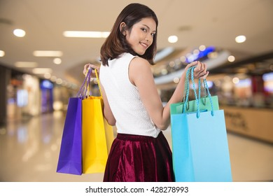 a happy woman with shopping bags  in modern shopping mall.