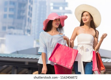 Happy woman with shopping bags pointing finger in the shop window Beautiful young couple carrying shopping bags and enjoying together.