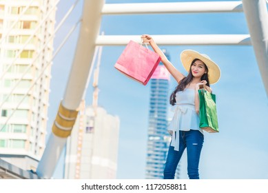Happy woman with shopping bags pointing finger in the shop window Beautiful young woman carrying shopping bags and enjoying for shopping. Traveling shopping in the city.