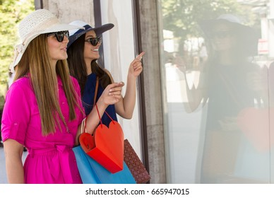 Happy woman with shopping bags pointing the finger at the shop window. Two beautiful young cheerful women holding shopping bags and looking at the shop window.