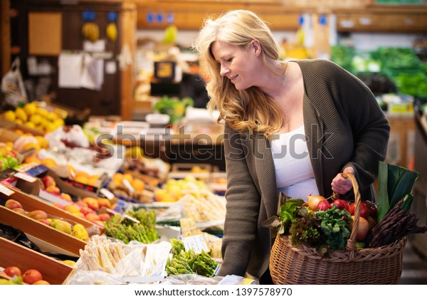 Happy woman is shopping fresh fruits and vegetables at the supermarket