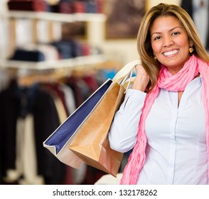 Happy woman shopping holding bags and smiling
