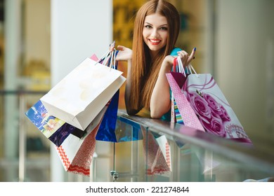 Happy woman shopping and holding bags at the mall. Shopping woman at the mall holding bags. Excited shopping woman holding bags with arms up