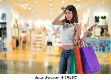 Happy woman shopping and holding bags at the mall
