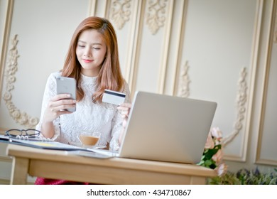 Happy woman shopping online, holding credit card, using laptop computer, electronic purchase.