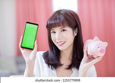 Happy woman show her pink piggy bank and smart phone with green screen